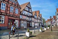 Celle, Alemanha - 1º de maio de 2017: Rua com a fachada da construção e do homem que montam uma bicicleta no Celle Cidade velha e Imagem de Stock Royalty Free