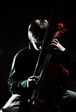 Cellist. Portrait of young cellist on black background Royalty Free Stock Images