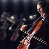 Cellist. Close-up of cellist playing classical music on cello in the orchestra royalty free stock images