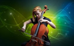 Cellist with colorful fabled concept. Serious classical cellist with fabled sparkling wallpaper royalty free stock photos