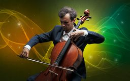 Cellist with colorful fabled concept. Serious classical cellist with fabled sparkling wallpaper royalty free stock images