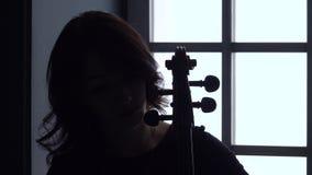 Cellist die een muzikale samenstelling op haar instrument spelen tegen het venster Sluit omhoog Silhouet stock footage