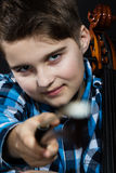 Cellist with fiddlestick. Young boy Cellist pointing with cello fiddlesticks royalty free stock photos