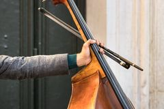 Cellist hand holding his violoncello and a bow outdoors in Venice, Italy. Cellist hand holding his violoncello and a bow outdoors in Venice stock photos