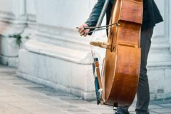 Cellist playing with a bow a cello outdoors in Venice, Italy royalty free stock photography