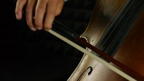 Cellist playing on cello. Strum the strings. stock footage