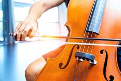 Close up of cello with bow in hands. Cellist playing violoncello musical instrument of orchestra royalty free stock image