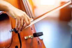 Close up of cello with bow in hands. Cellist playing violoncello musical instrument of orchestra stock image