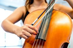 Close up of cello with bow in hands. Cellist playing violoncello musical instrument of orchestra stock images