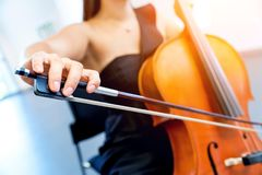 Close up of cello with bow in hands. Cellist playing violoncello musical instrument of orchestra stock photography
