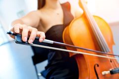 Close up of cello with bow in hands. Cellist playing violoncello musical instrument of orchestra royalty free stock images