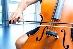 Close up of cello with bow in hands. Cellist playing violoncello musical instrument of orchestra royalty free stock photos