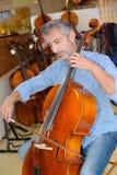 Cellist testing the cello. Cello royalty free stock photography