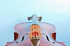 Cello against blue. A classic wooden cello string instrument against a blue backdrop royalty free stock photos
