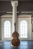 Cello in an ampty vintage Location. A cello laying on a column in an industrial vintage location Royalty Free Stock Photo