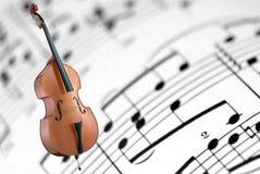 Cello auf einem weißen Blattmusikhintergrund Lizenzfreies Stockfoto