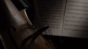 Cello close up of bows carry on the back of the string sheets with notes. Side view. Cello close up of bows carry on the string behind the sheets with notes in a stock video footage