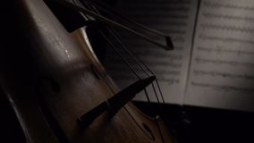 Cello closeup with sheets of notes. Close up. Side view. Cello closeup in a dark room with sheets of notes. Close up. Side view stock footage