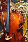 Cello with a Fall Thanksgiving Look. A cello with straw and a fall or Thanksgiving flavor in the vertical view Royalty Free Stock Photography