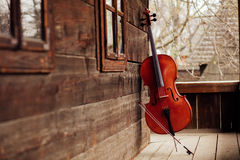 Cello leaning on a porch. Cello leaning on a wooden old porch royalty free stock image