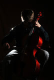 Cello player. On black background Royalty Free Stock Photo