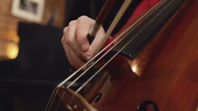 Cello player. Cellist hands playing cello with bow. And pianist stock footage