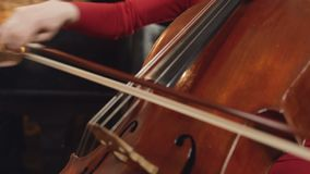 Cello player. Cellist hands playing cello with bow. Violoncello orchestra musical instrument closeup. stock footage