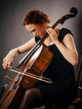 Cello player concentrating on her playing. Photo of a beautiful woman concentrating on her cello playing Royalty Free Stock Photos