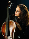 Cello player and her instrument. Photo of a beautiful woman posing with her old cello Stock Photography