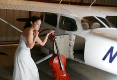 Cello Trouble. Beautiful woman with a puzzled look trying to figure out how to load a cello into a light airplane baggage compartment Royalty Free Stock Image