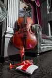 Cello and two red wineglasses on the pillow royalty free stock photography