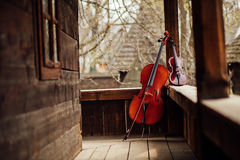 Cello and violin leaning on a porch Stock Image