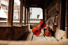 Cello and violin leaning on a porch Royalty Free Stock Photography