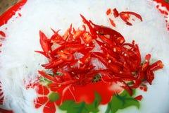 Cellofaannoedels en rode die Spaanse pepers op dienblad worden gesneden stock afbeeldingen