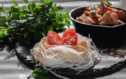 Cellofannudlar med halvan av tomaten, löken och persiljan på brädet av svart kritiserar royaltyfri bild