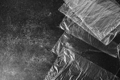 Black and white art monochrome photography. Cellophane bags on a dark marble background. Polute the nature. Eco concept Stock Images
