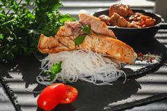 Cellophane rice vermicelli with slices of grilled salmon with tomatoes, onion and parsley on the Board of black slate. Close-up. Stock Photos