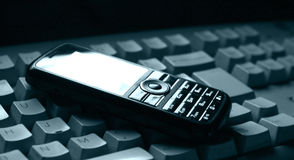 Cellphone. Mobile phone and computer keyboard Stock Image