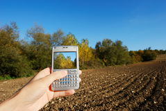 Cellphone and autumn landscape royalty free stock photos