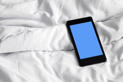Cellphone on bed sheets Stock Images