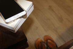 Cellphone and books on nightstand at night time Royalty Free Stock Images