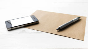 Cellphone with brown paper and pen Stock Images