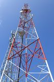 Cellphone communication. A tall Telecommunication tower in red and white on a blue background stock photo