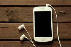 Cellphone. And earphones on wood texture Stock Image