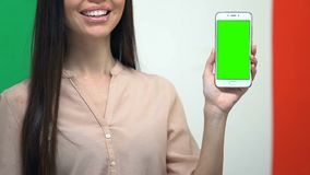 Cellphone with green screen in female hand against Italian flag, translator app. Stock footage stock video footage