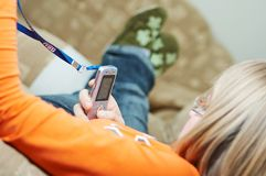 Cellphone held by teenager. Cellphone held by blond caucasian teenager. Shallow DOF. Only mobile phone is in focus Royalty Free Stock Image