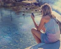 cellphone Jeune femme s'asseyant par le rivage avec le téléphone portable Photos stock
