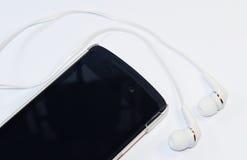 Cellphone met oortelefoons stock foto's
