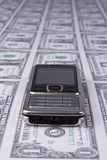 Cellphone on money background Royalty Free Stock Image