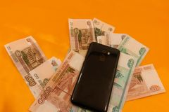 Cellphone on the Russian Currency Background bank.  royalty free stock photo